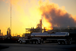 Large liquid transport truck parked in front of a refinery at sunset
