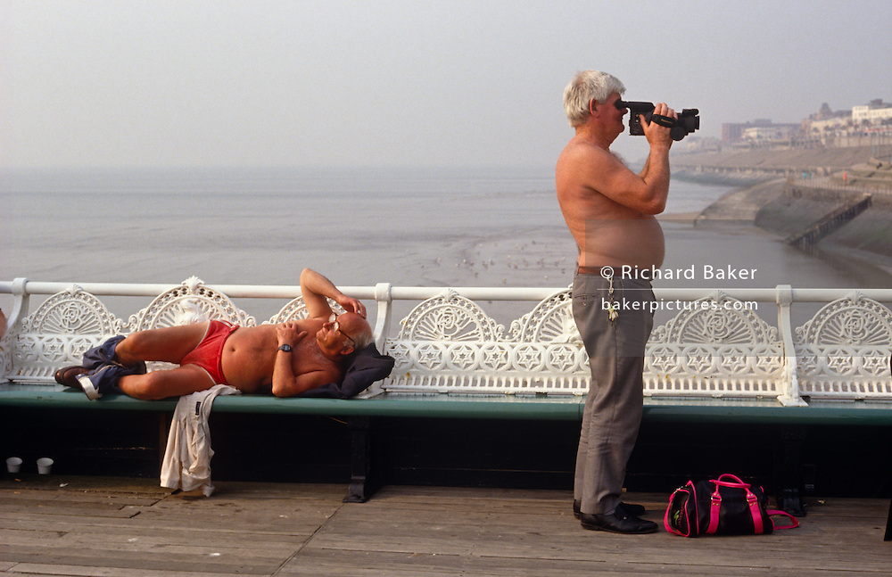 Two men enjoy their own versions of Blackpool North Pier, Lancashire, England. On the right, the first man is lying down on a bench with his trousers gathered around his ankles, his red bathing costume or underpants are baggy and he is looking across to something of interest while scratching his bald head. The second man on the right is not wearing a shirt and his stomach is spilling over his trousers. He has a bunch of keys attached to his belt and is pointing a video camera (camcorder) towards the shore. It is a comical scene and typical of Blackpool beach life. This northern sea side resort in the north-west of England is diverse in its transient holiday population whose behaviour can be routinely odd.