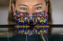 "© Licensed to London News Pictures. 19/03/2021. LONDON, UK. A staff member poses views ""A pair of jewelled gold and enamel elephants, Jaipur, 1946 (est. £2,000-3,000).  Preview of the upcoming sale of property from the collection of the Patricia Knatchbull, 2nd Countess Mountbatten of Burma.  Over 350 lots spanning jewellery, furniture, paintings, sculpture, books, silver, ceramics & objets d'art are to be auctioned on 24 March at Sotheby's New Bond Street galleries.  Photo credit: Stephen Chung/LNP"