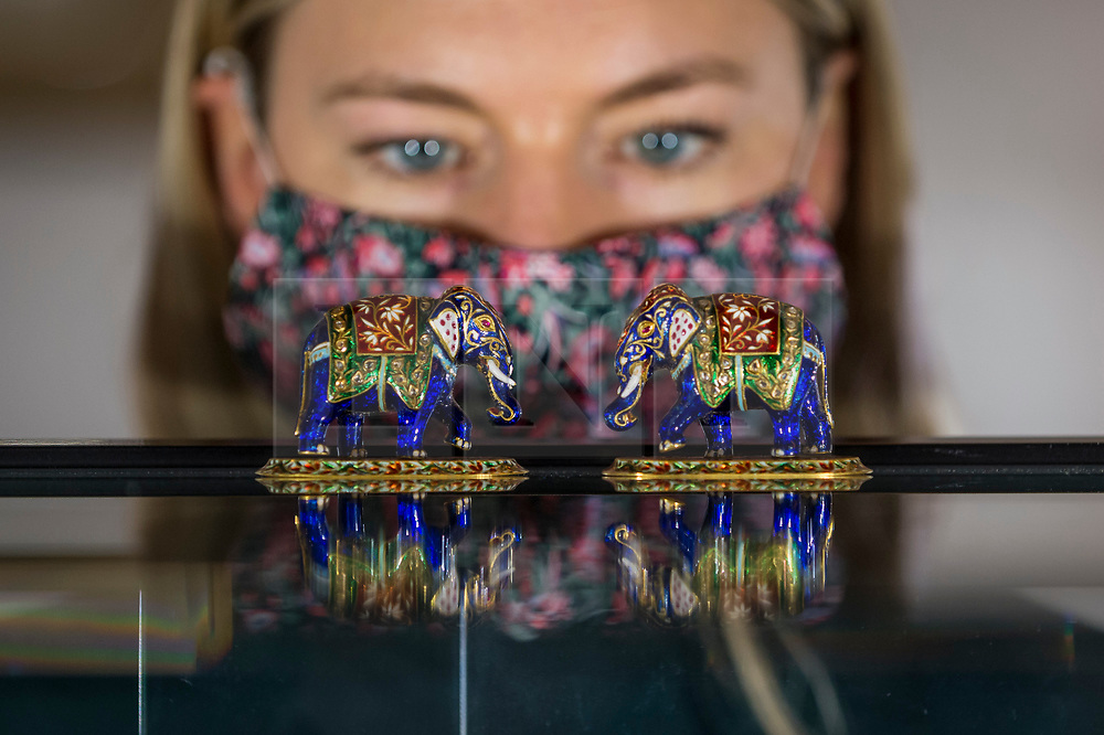 """© Licensed to London News Pictures. 19/03/2021. LONDON, UK. A staff member poses views """"A pair of jewelled gold and enamel elephants, Jaipur, 1946 (est. £2,000-3,000).  Preview of the upcoming sale of property from the collection of the Patricia Knatchbull, 2nd Countess Mountbatten of Burma.  Over 350 lots spanning jewellery, furniture, paintings, sculpture, books, silver, ceramics & objets d'art are to be auctioned on 24 March at Sotheby's New Bond Street galleries.  Photo credit: Stephen Chung/LNP"""