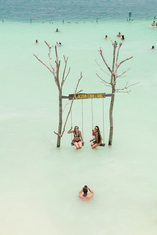 Tulum, Mexico - June 6, 2021: Visitors to Kaan Luum Lagoon outside Tulum pose for a classic photo on swings above the water.