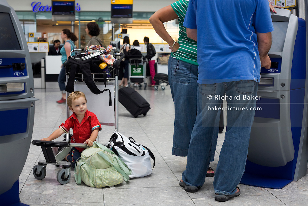 A scene of busy modern air travel as international passengers check-in at the British Airways Heathrow Airport's T5.