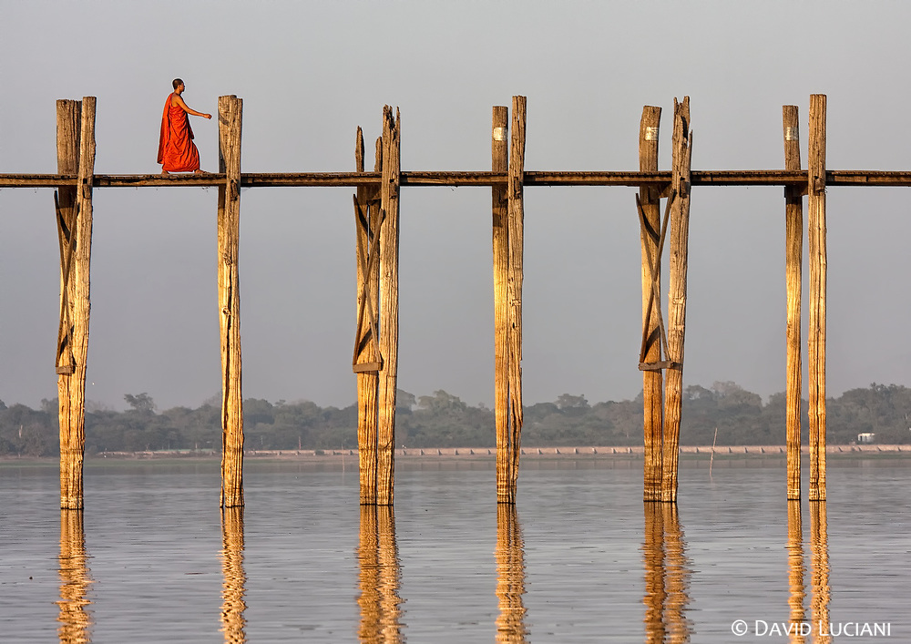 A monk crossing the U Bein Bridge shortly before sunset.
