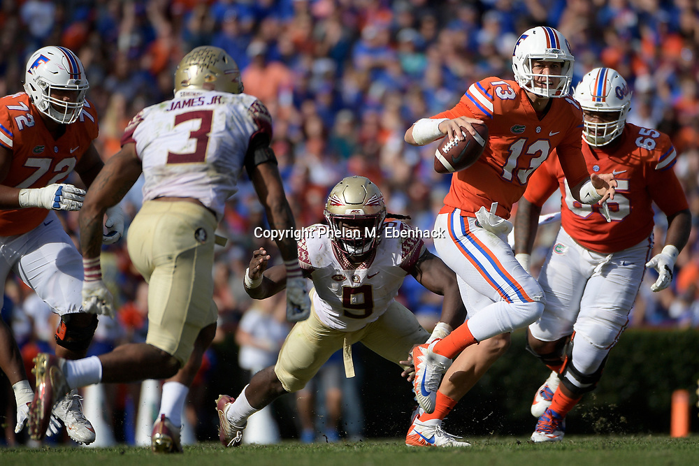 Florida quarterback Feleipe Franks (13) scrambles in front of Florida State defensive back Derwin James (3) during the second half of an NCAA college football game Saturday, Nov. 25, 2017, in Gainesville, Fla. FSU won 38-22. (Photo by Phelan M. Ebenhack)
