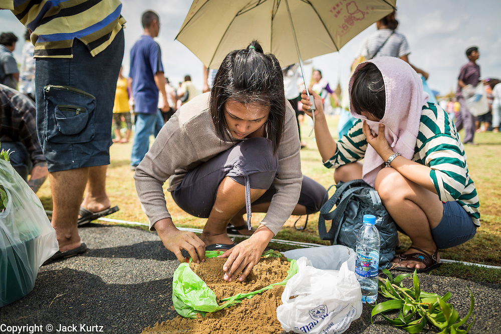 13 MAY 2013 - BANGKOK, THAILAND:  Women sift through the sand looking for rice seeds blessed by Brahmin priests at the Royal Ploughing Ceremony. After the ceremony, thousands of Thais, mostly family formers, rush onto the ploughed ground to gather up the blessed rice seeds sown by the Brahmin priests. The Royal Plowing Ceremony is held Thailand to mark the traditional beginning of the rice-growing season. The date is usually in May, but is determined by court astrologers and varies year to year. During the ceremony, two sacred oxen are hitched to a wooden plough and plough a small field on Sanam Luang (across from the Grand Palace), while rice seed is sown by court Brahmins. After the ploughing, the oxen are offered plates of food, including rice, corn, green beans, sesame, fresh-cut grass, water and rice whisky. Depending on what the oxen eat, court astrologers and Brahmins make a prediction on whether the coming growing season will be bountiful or not. The ceremony is rooted in Brahman belief, and is held to ensure a good harvest. A similar ceremony is held in Cambodia.   PHOTO BY JACK KURTZ