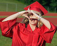 A Port Jervis senior makes a heart with her hands while walking around the track at the start of graduation ceremonies for the Port Jervis High School Class of 2012 on Friday, June 22, 2012.