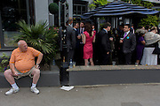 Man with large belly touts for tickets next to a society bar in the street during the annual Royal Ascot horseracing festival in Berkshire, England. Royal Ascot is one of Europe's most famous race meetings, and dates back to 1711. Queen Elizabeth and various members of the British Royal Family attend. Held every June, it's one of the main dates on the English sporting calendar and summer social season. Over 300,000 people make the annual visit to Berkshire during Royal Ascot week, making this Europe's best-attended race meeting with over £3m prize money to be won.