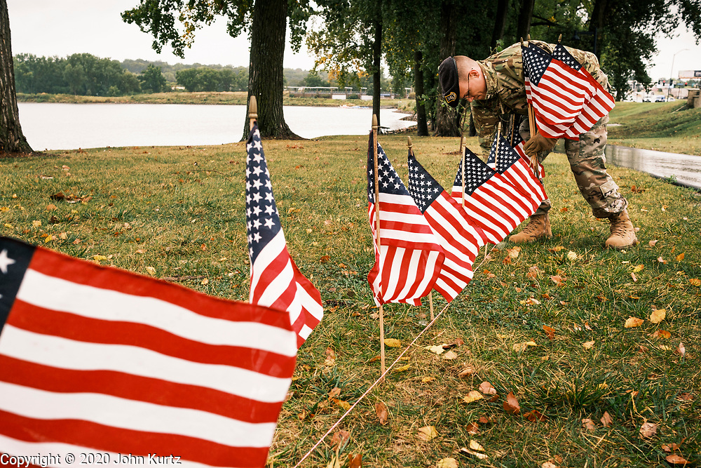 10 SEPTEMBER 2020 - DES MOINES, IOWA: S Sgt. SAMUEL ESKELSON, US Air Force, right, sets American flags on the shore of Gray's Lake. About 25 volunteers braved cold and rainy weather Thursday to line the west end of Gray's Lake in Des Moines with American flags. The display of flags was a part of an annual event called the 9/11 Tribute Trail. About 3,000 flags were set out in memorial of the 3,000 people killed in the 9/11 terrorist attacks.     PHOTO BY JACK KURTZ
