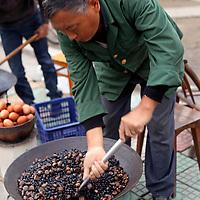 Asia, China, Yichang. Vendor roasts hazelnuts in Yichang.