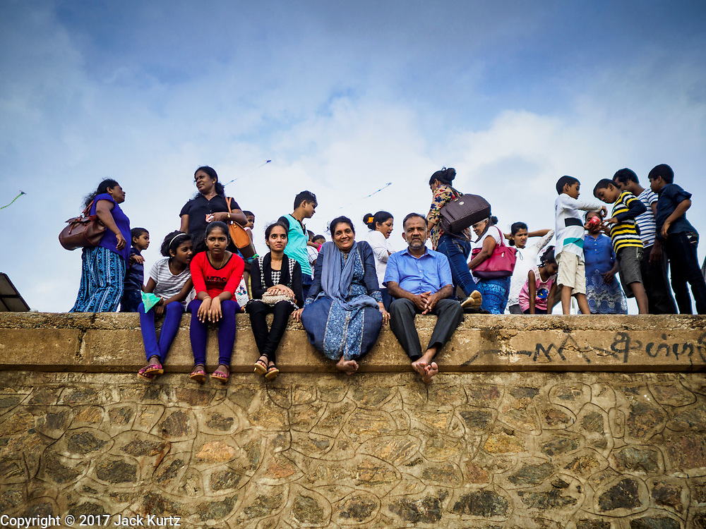 05 OCTOBER 2017 - COLOMBO, SRI LANKA: People sit on the sea wall at Galleface in Colombo, Sri Lanka.     PHOTO BY JACK KURTZ
