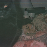 1. When was this photo taken?<br /> <br /> 1995 or 1996<br /> <br /> 2. Where was this photo taken?<br /> <br /> Syracuse, New York<br /> <br /> 3. Who took this photo?<br /> <br /> Paul Maliszewski<br /> <br /> 4. What are we looking at here?<br /> <br /> This is a picture of Monique, my girlfriend at the time, asleep, with our two cats. Charlie is snuggled into the blankets, and Kelly is sitting up, looking back at me.<br /> <br /> 5. How does this old photo make you feel?<br /> <br /> Oh, a mixture--a little happy, a little sad, but glad to have the photo. It's like getting back an old memory.<br /> <br /> 6. Is this what you expected to see?<br /> <br /> I figured the roll of film was from when I lived in Syracuse, but I didn't know what to expect. I wasn't sure any pictures would come out, after all these years. I hadn't exactly taken care of the film. It was just sitting in my desk; I'd moved with it several times.<br /> <br /> 7. What kind of memories does this photo bring back?<br /> <br /> A lot of fond sensory memories. Just the way the things in the photo evoke, for me, our apartment. The floral comforter, the flannel sheets. It must have cold. Monique's lamp. Even that plastic cup on her nightstand. Charlie always liked to snuggle.<br /> <br /> 8. How do you think others will respond to this photo? <br /> <br /> I don't know. To me, it's so personal. To someone else, I don't know what someone else will think.