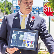 John Fraser Bryan American Legion Post # 19 Commander, Earl Menard, holds a photo of Coxswain Dominick Farina, who fell in the closing days of WWI.