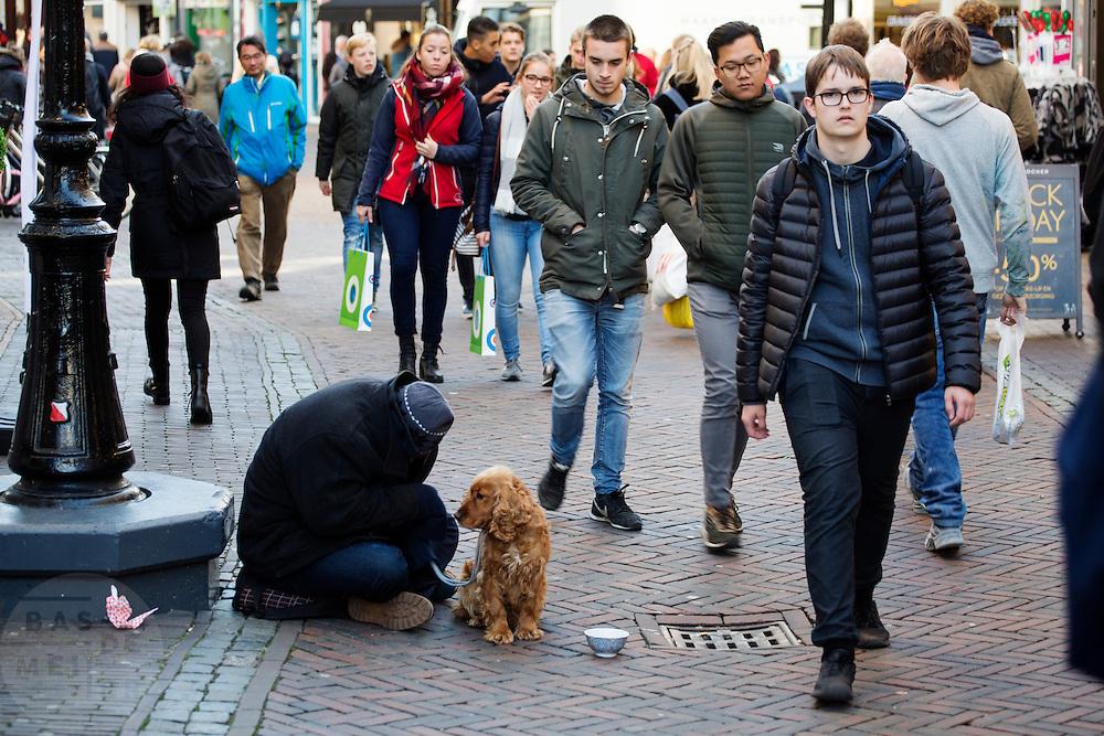 In Utrecht zit een bedelaar op de grond met zijn hond. De bedelaars zijn een doorn in het oog van veel Utrechtse winkeliers. Het gaat vaak om Roemenen en Bulgaren die georganiseerd aan het werk gaan.<br /> <br /> Utrecht a beggar sits on the ground with his dog. The beggars are a thorn in the side of many Utrecht retailers. It often involves Romanians and Bulgarians who operate organized.