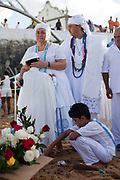 Young boy sitting on the floor as part of a Candomble group in traditional white dress preparing for a public ceremony on the beach. February 2nd is the feast of Yemanja, a Candomble Umbanda religious celebration, where thousands of adherants visit the Rio Vermehlo Red River to make offerings of flowers and prayers, paying their respects to Yemanja, the Orixa goddess of the Sea and water.