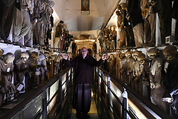 NO WEB FOR FRANCE - A monk in the Capuchin Catacombs of Palermo, Sicily, Italy on January 2019. The catacombs contain about 8000 corpses and 1252 mummies. Palermo's Capuchin monastery outgrew its original cemetery in the 16th century and monks began to excavate crypts below it. In 1599 they mummified one of their number, recently dead brother Silvestro of Gubbio, and placed him into the catacombs. The cemetery was first reserved for ecclesiastical workers, then accepted deceased from all walks of life, and experienced its greatest popularity during the 19th century. An inscription hanging from the neck or pinned to the chest, indicates the name, birth and death dates of the deceased.The cemetary was officially closed by civil order in 1880. But the last burials are from the 1920s. The cemetary has now become a kind of museum, filled with the forgotten dead, who are watched over by a group of Capuchin monks. Sicily will reveal over time a real research laboratory on mummification. It is spreading throughout the island and there is not an important village in sight that does not display the bodies of their priests, monks or citizens in the crypt of their church. Photo by Eric Vandeville/ABACAPRESS.COM