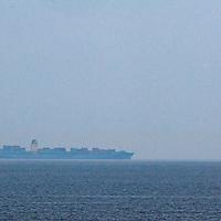 A container ship freighter cruises through fog along the California Pacific Ocean coast en route to San Francisco.