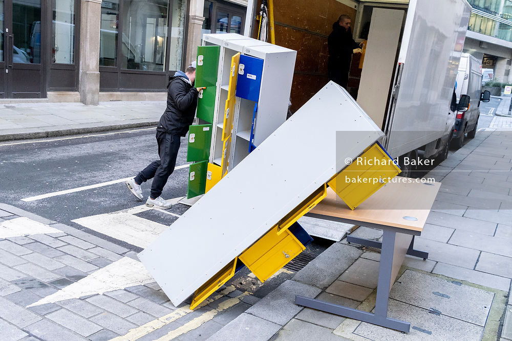 A contractor struggles with unstable office locker furniture being removed from from a nearby building during the third lockdown of the Coronavirus pandemic, in the City of London, the capital's financial district, on 10th February 2021, in London, England.