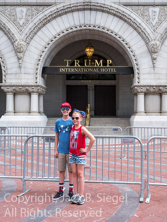 """Two children stand in front of the Trump International Hotel in Washington, D.C. while an adult snaps a picture.  The boy is wearing a """"Make America Great Again"""" Hat"""