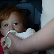 A baby nursing on a bottle on the train in Monterosso, Italy