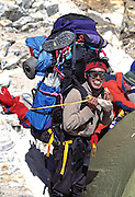 A climbing Sherpa prepares to carry a giant load during an expedition to Pumori Peak in the Everest Region of the Himalaya, Nepal.