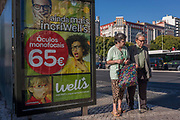 An elderly couple walk slowly past an advert for spectacles oculos from the Portuguese retailer Wells, on 14th July 2016, in Lisbon, Portugal. The street is busy with rush hour traffic at Alameda underground Metro station and the wife helps her inform husband to walk with the aide of a stick.