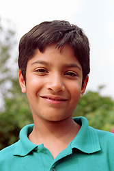 Portrait of boy standing outdoors smiling,