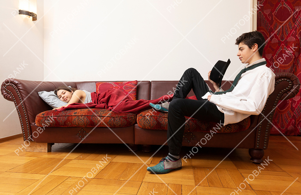 Girl lying on the sofa with a blanket and a young boy is sitting desperately dressed elegantly