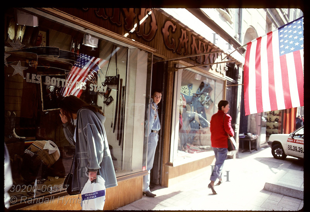 Woman peeks in window at store specializing in cowboy boots as US flag waves above; Strasbourg. France