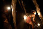 Shirtless miners working in total darkness with primitive equipment in the Karkara coal mine.