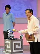 """A presenter smashes a fake vase with a golden hammer on the set of """"Collector's World,"""" a Beijing Television game show. Participants bring their antiques to be appraised by experts and if the articles are deemed to be fakes they are smashed with a golden hammer. The show plays on the country's turbulent modern history, and on the widespread fear of being deceived in a country where everything from DVDs to drugs can be faked."""
