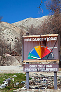 Fire danger sign with wildfire damage in background. Hidden Springs Fire Station was protected by efforts of firefighters, but surrounding area was completely burned. April, 2010, about six months after the Station Fire. The Station fire, the tenth largest wildfire in California History burned over 160,000 acres from late August to mid October 2009. Angeles Forest Highway, Angeles National Forest, Los Angeles County, California, USA