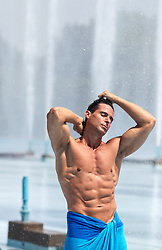 hot bodybuilder wrapped in a small towel by an outdoor fountain