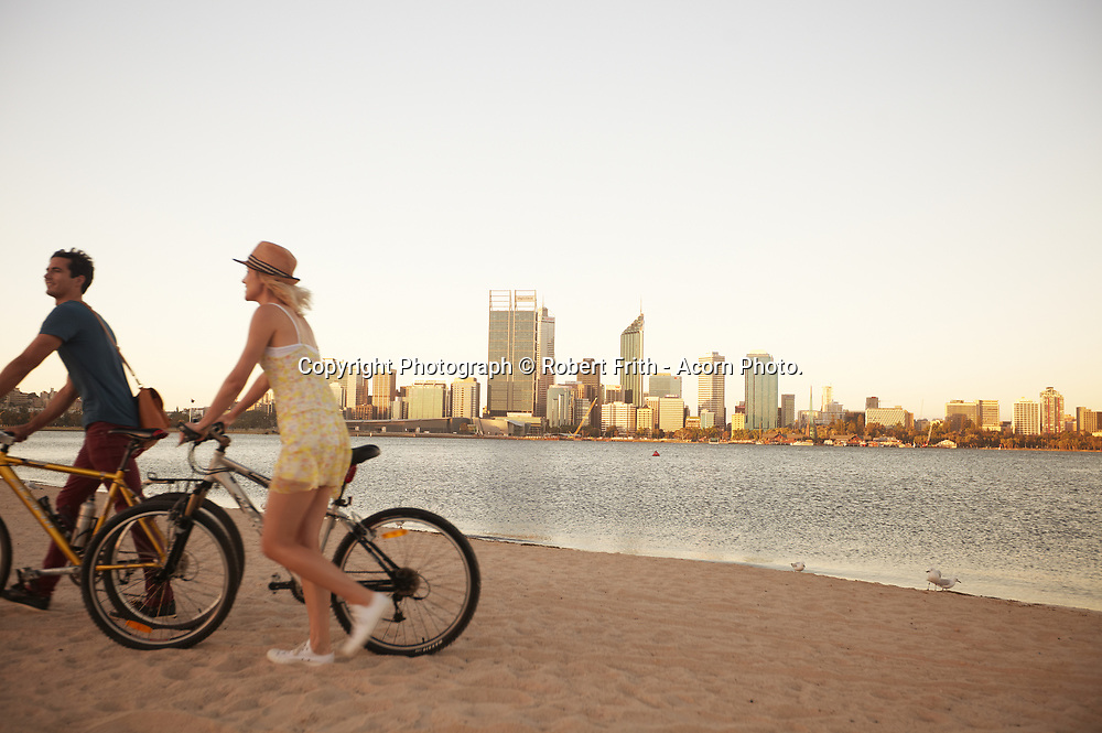Sunset view with cyclists <br /> from South Perth across the Swan River to the Perth central business district