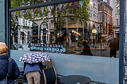 """In front of a cafe whose slogan is """"Here's to a Long Cold Summer"""", an anonymous person bends over while holding an umbrella during Spring rainfall in Holborn, on 24th May 2021, in London, England."""