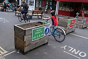 A blurred young cyclist passes through the barriers that form an LTN (Low Traffic Neighbourhood), an experimental closure by Southwark Council preventing motorists from accessing the junction of Carlton Avenue and Dulwich Village. Restrictions also prevent traffic from passing through at morning and afternoon rush-hour times in the borough of Southwark, on 14th June 2021, in London, England.