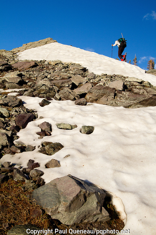 A backpacker in plastic mountaineering boots acends a snowfield in Glacier National Park.