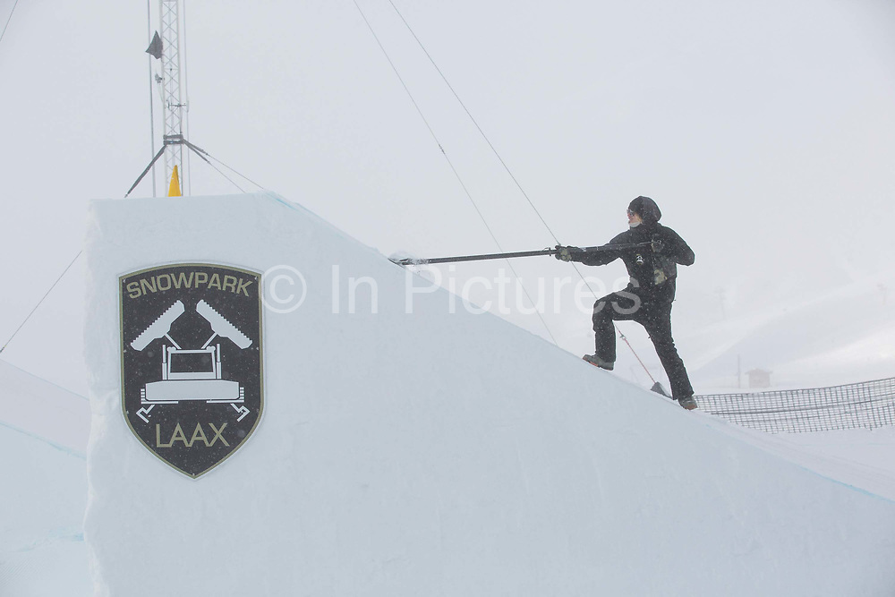 A park shaper scraps snow from a jump for the Laax Open on 17th January 2017 in Laax, Switzerland. The Laax Open is a FIS Snowboarding World Championship event in Laax.
