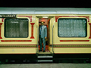 A manager waits for guests on the Palace on Wheels, a vintage luxury train crossing Rajahstan province.