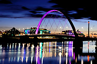 The Clyde Arc, also known as the Squinty Bridge, is lit up as night falls with STV and BBC offices in the background and the lights reflecting on the River Clyde