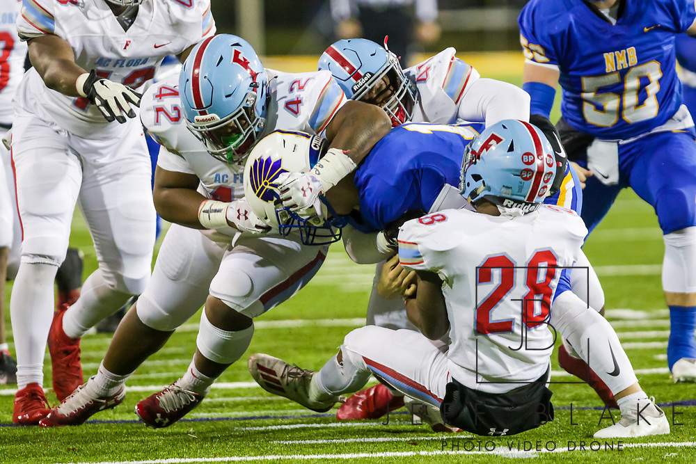 AC Flora Falcons defensive lineman Jaylin Brown (42), AC Flora Falcons defensive lineman Amoree' Stephens (41) and AC Flora Falcons Markel Townsend (28) sack North Myrtle Beach Chiefs quarterback Cameron Freeman (10) during the first half the state championship game at Benedict College.