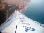 Alitalia passenger jet wing and logo during flight