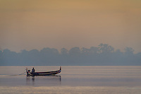 MANDALAY, MYANMAR - CIRCA DECEMBER 2013:  Typical boat crossing the Taungthaman Lake early morning near Mandalay