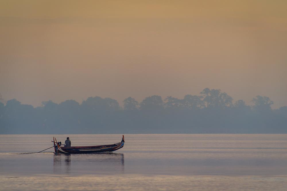 MANDALAY, MYANMAR - CIRCA DECEMBER 2013:  Typical boat crossing the Taungthaman Lake early morning near Mandalay