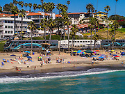 """26 JUNE 2012 - SAN CLEMENTE, CALIFORNIA: The Metrolink train rolls past San Clemente, CA. San Clemente is midway between Los Angeles and San Diego at the southern tip of Orange county. It is known for its ocean, hill, and mountain views, a pleasant climate and its Spanish Colonial style architecture. San Clemente's city slogan is """"Spanish Village by the Sea"""".  PHOTO BY JACK KURTZ"""