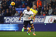 Craig Davies of Bolton Wanderers and Mark Hudson of Huddersfield Town battle for the ball. Skybet football league championship match, Bolton Wanderers v Huddersfield Town at the Macron stadium in Bolton, Lancs on Saturday 29th November 2014.<br /> pic by Chris Stading, Andrew Orchard sports photography.
