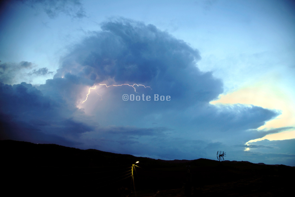 approaching storm with a lightning bolt during sunset