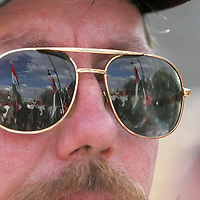 Flags form a political demonstration are reflected on the sunglasses of a participant.