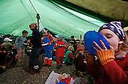 Svizzera, San Gallo, asilo nel bosco , un piccolo casottino in legno è il rifugio in caso di forte pioggia...le lezioni solitamente si volgono sempre all'aperto per tutto l'inverno .  children are even involved in cooking the lunch...lunch in the tent....Switzerland, St. Gallen, kindergarten in the wood. Children are free to run and enjoy in the wood no matter cold or snow... lunch in the tent...
