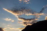 Sunset clouds form lips in a mouth-shaped pattern in blue sky above Slovenia, Europe.