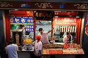 """Chinese cities are among the world capitals of street food, with stands selling an extraordinary variety of treats. In central Beijing, the Enrong Roasted Meat Store offers """"Brazilian roasted meat"""" (left foreground, the vertical, rotating stack of meat), """"fresh-boiled"""" and """"honey-roasted"""" corn on the cob, """"Mongolian grasslands roasted meat,"""" dry, tire-black """"stinky tofu,"""" and a rack of skewered scorpions (under salesman's outstretched arm). Hungry Planet: What the World Eats (p. 77). This image is featured alongside the Dong family images in Hungry Planet: What the World Eats."""